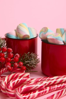 High angle view of cropped image of christmas items, striped sugary candy canes, holly and cup with hot drink and wet colorful marshmallows on pink colored background with copy space for christmas ad