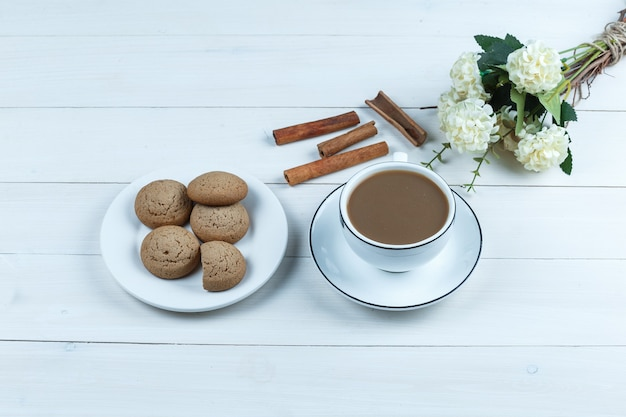 High angle view cup of coffee with flowers, cinnamon, cookies on white wooden board background. horizontal