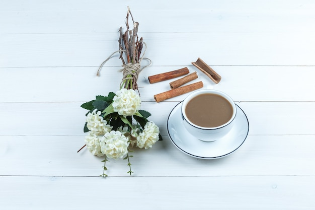 High angle view cup of coffee with flowers, cinnamon on white wooden board background. horizontal