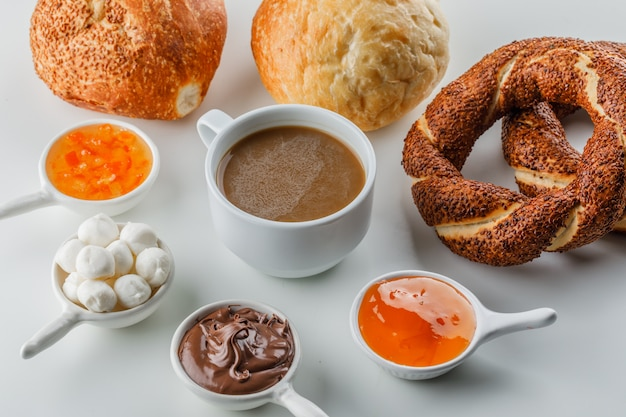 High angle view a cup of coffee with jams, sugar, chocolate in cups, turkish bagel, bread on white surface