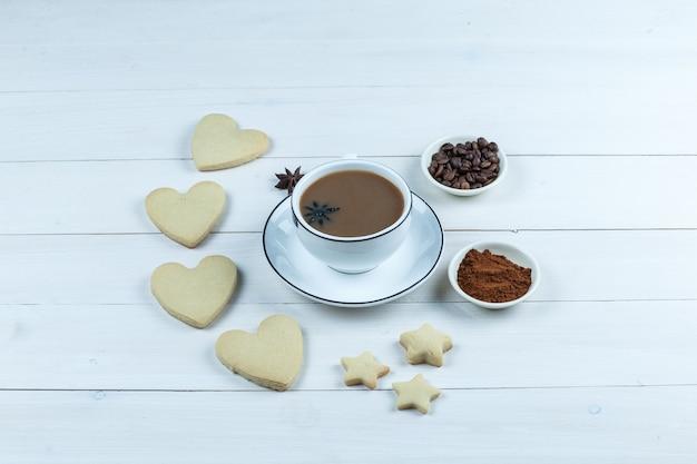 Чашка кофе с высоким углом обзора с печеньем, кофейными зернами и растворимым кофе на фоне белой деревянной доски. горизонтальный