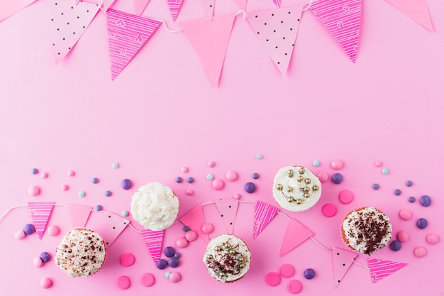 High angle view of cupcakes; candies and bunting on pink background