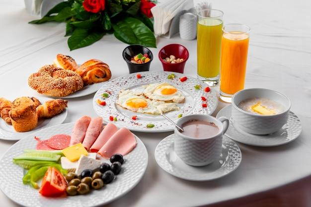 ハイアングルは、サラダ、目玉焼き、白い背景の上のペストリーのテーブルでおいしい朝食を表示します。横型