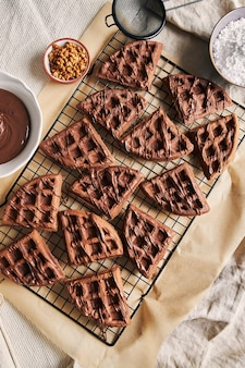 High angle view of delicious chocolate waffles on a net on the table near the ingredients