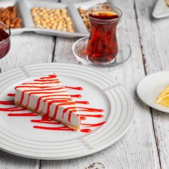 Dessert delizioso di vista dell'angolo alto in piatto con tè, noci, marmellata di frutta, limoni affettati su fondo di legno bianco.