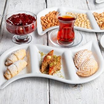 Dessert deliziosi di vista dell'angolo alto con tè, noci, marmellata di frutta su fondo di legno bianco.