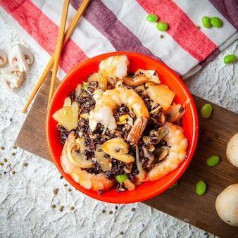 Взгляд высокого угла очень вкусная еда в красной плите с crevettes на древесине, ткани и белой текстурированной предпосылке.