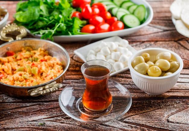 Pasto delizioso di vista dell'angolo alto in piatto con una tazza di tè, insalata, sottaceti su superficie di legno