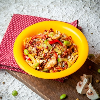 Pasto delizioso di vista dell'angolo alto in piatto giallo su legno, panno rosso e fondo strutturato bianco.