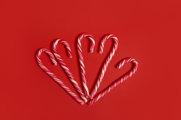 High angle view of delicious sweet christmas candy canes on red background with copy space for christmas advertising. decoration for 25 december