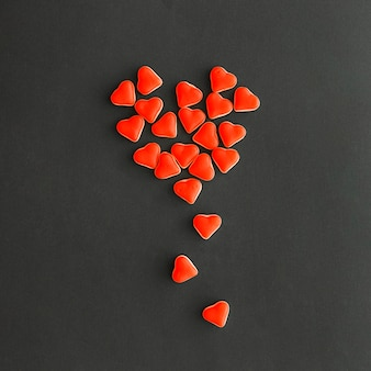 High angle view of design made with tiny red heart shape candies on black backdrop