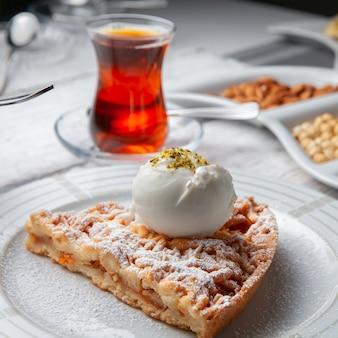 Dessert di vista dell'angolo alto in piatto con tè, dadi su fondo di legno bianco.
