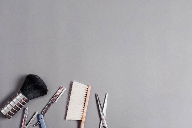 High angle view of different barber tools over grey backdrop