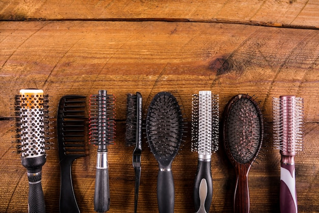 High angle view of different hairbrushes on wooden backdrop