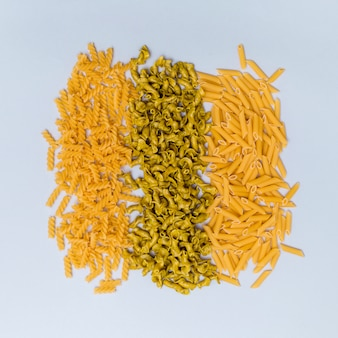 High angle view of different shape pasta arrange in a row on gray surface
