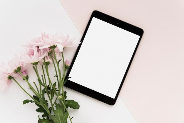 High angle view of digital tablet and bunch of flowers on dual background