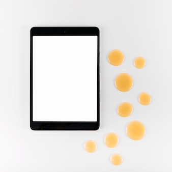 High angle view of digital tablet and drop of honey on white background