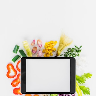 High angle view of digital tablet on fresh healthy vegetables