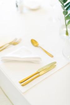 フォーク、ナイフ、スプーンを備えたハイアングルのダイニングテーブル。垂直