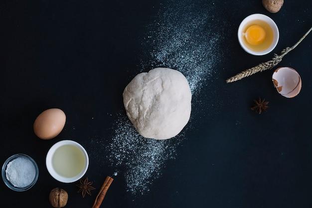 Vista dell'angolo alto di pasta con gli ingredienti di cottura sul contesto nero