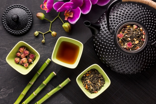 High angle view of dried herb ingredient and bamboo stick with orchid flower