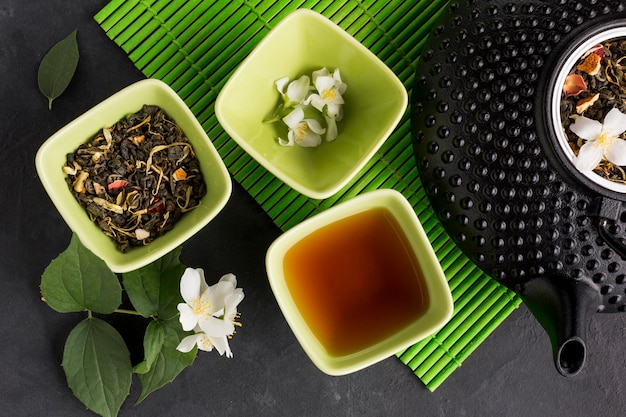 High angle view of dried herb and white jasmine flower teapot on slate stone background