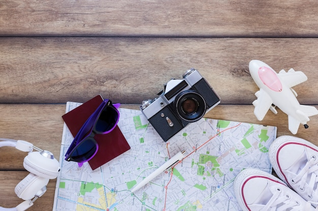 High angle view of earphone; passport; sunglasses; map; pen; camera; footwear and airplane on wooden backdrop