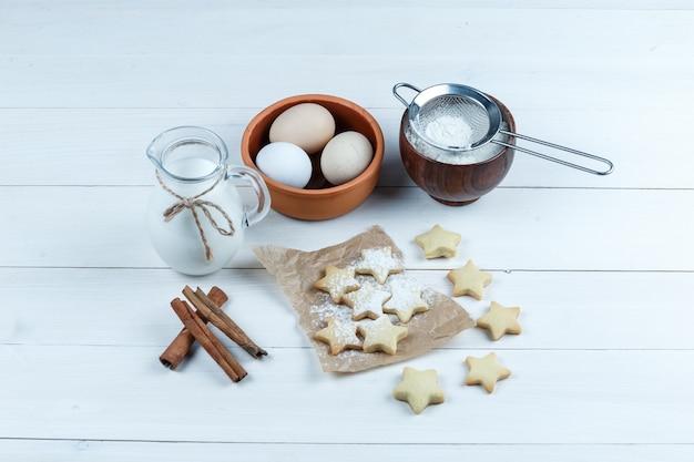 Uova di vista di alto angolo nella ciotola con biscotti, bastoncini di cannella, latte, zucchero in polvere su fondo di legno.