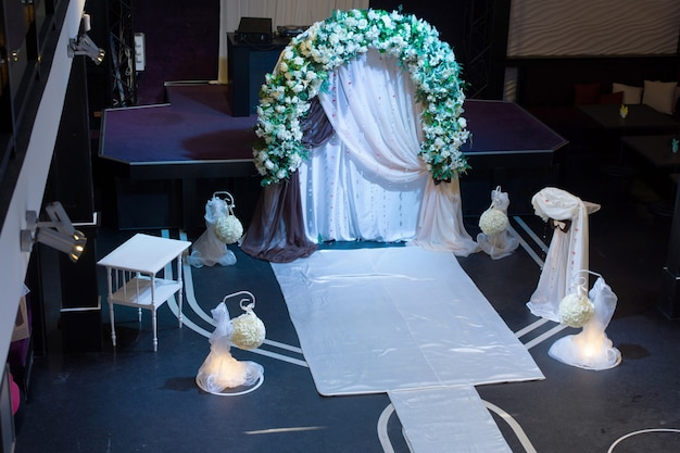High angle view on elegantly styled unique wedding arrangements in empty dimly lit room with flowers on arch
