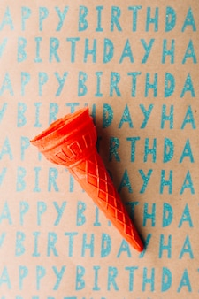 High angle view of empty ice cream cone on happy birthday gift paper