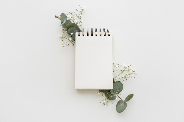 High angle view of empty spiral notepad with leafs and baby's breath flowers on white surface