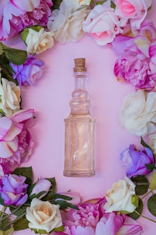 High angle view of essential oil surrounded with fresh flowers on pink background