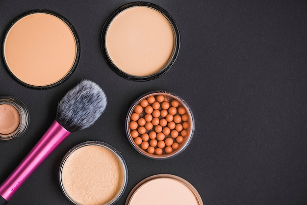 High angle view of face powder; bronzing pearls and makeup brush on black backdrop