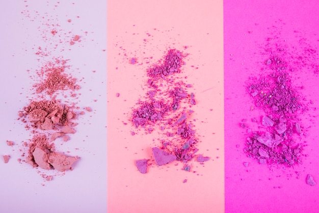 High angle view of face powders on colorful background