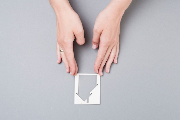 High angle view of female hand touching house cutout on grey background
