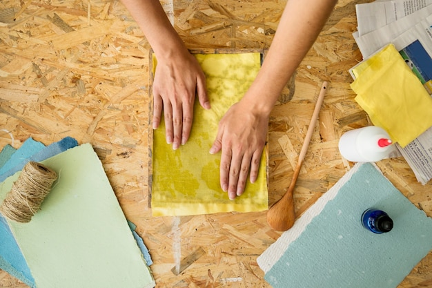 High angle view of a female's hand covering paper pulp with yellow cloth