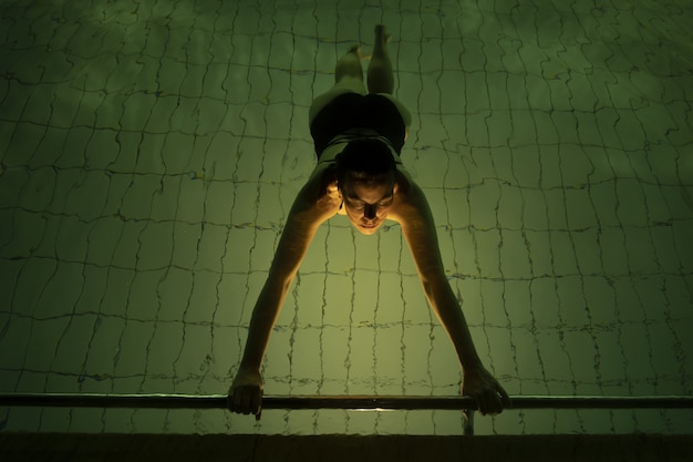 High angle view of a female swimming in a pool under the lights - perfect for sport concepts