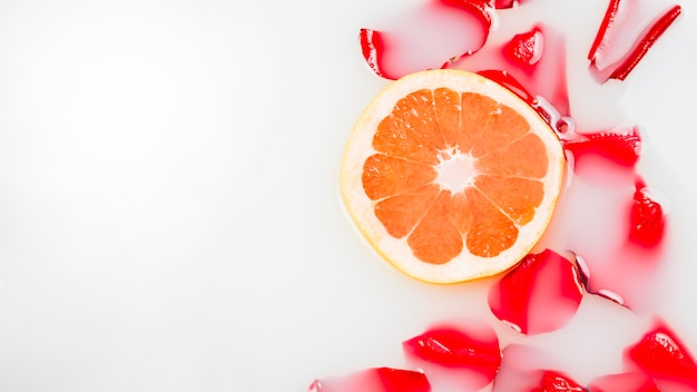 High angle view of flower petals and slice of grapefruit floating on milk