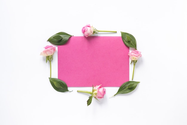High angle view of flowers and leaves surrounding blank pink paper on white surface