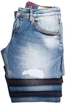 High angle view of folded and stacked blue jeans - looking down at denim pants in varying color washes and styles in neat stack on white background