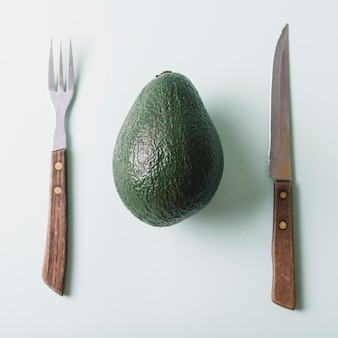 High angle view of fresh avocado; knife and fork on green surface