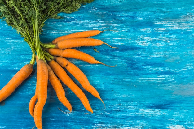 High angle view of fresh carrots on blue wooden backdrop