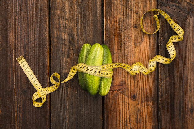 High angle view of fresh cucumbers and measuring tape on wooden background