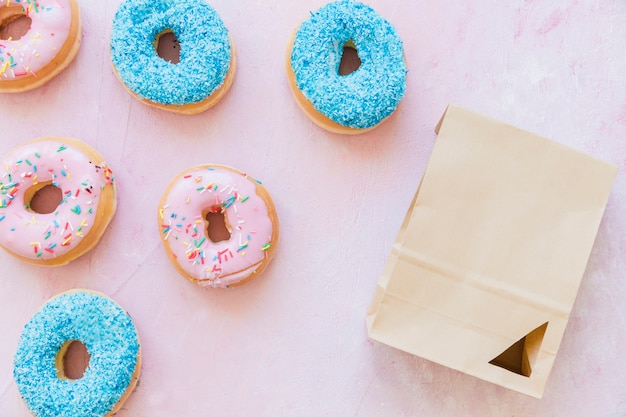 High angle view of fresh donuts and package on pink background