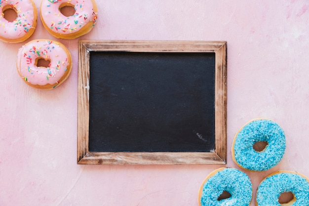 High angle view of fresh donuts with blank black slate on pink backdrop