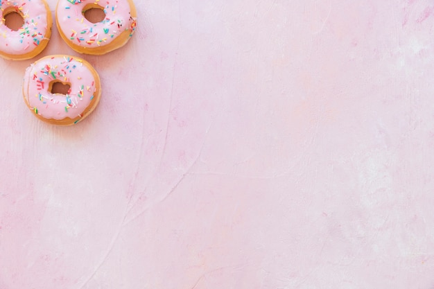 High angle view of fresh donuts with sprinkles on pink background