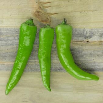 High angle view of fresh green chili peppers on wooden backdrop