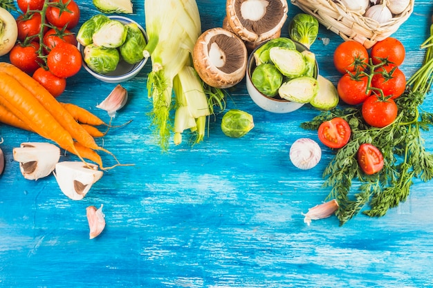 High angle view of fresh organic vegetables on blue wooden backdrop