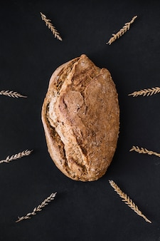 High angle view of freshly baked bread surrounded by grains on black background