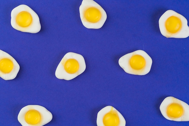 High angle view of fried egg gummies on blue background